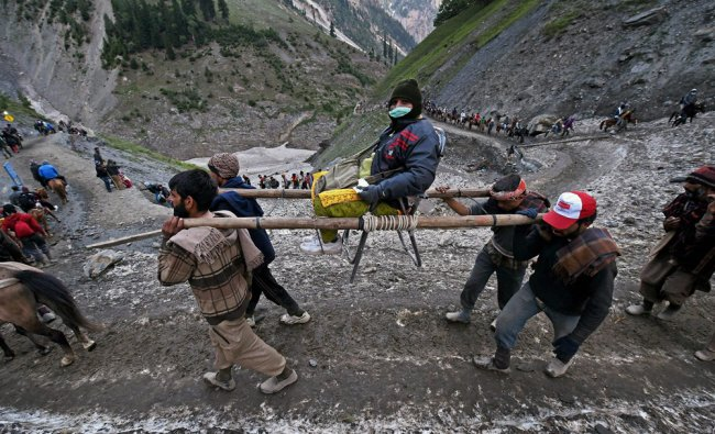 Local labourers carry a female devotee in a make-shift palanquin en route Amarnath Cave Shrine ...