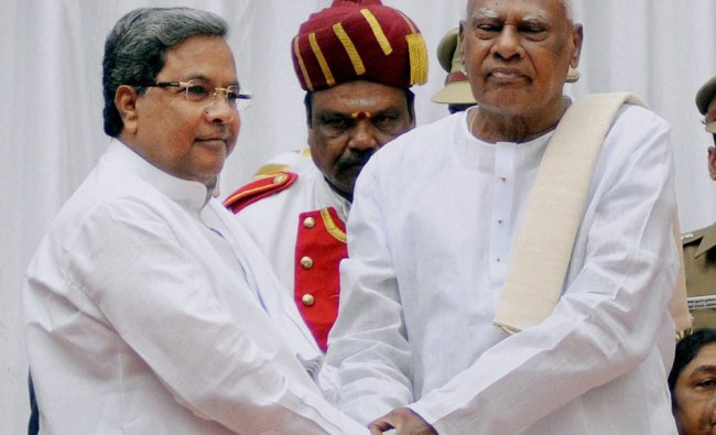 Siddaramaiah greets Karnataka Governor in-charge, K Rosaiah during the swearing in ceremony ...
