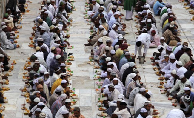 Muslims sit before having their Iftar (evening breaking fast) meal on the first day of the holy...