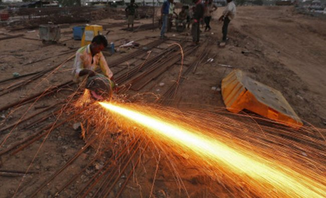 A labourer cuts an iron rod at the construction site of a flyover on the outskirts of Ahmedabad...