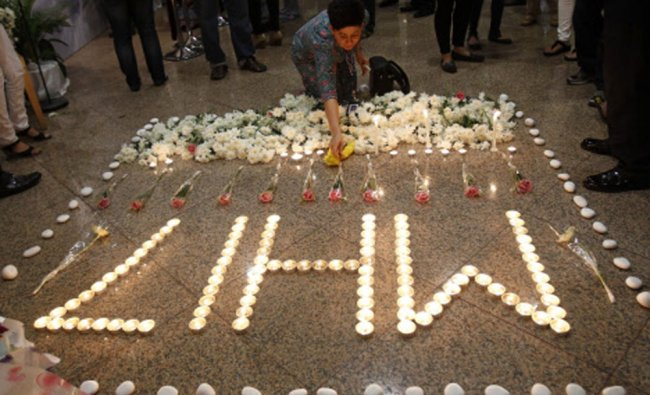 A Malaysia Airlines crew member places a flower next to candles forming the letters MH17...