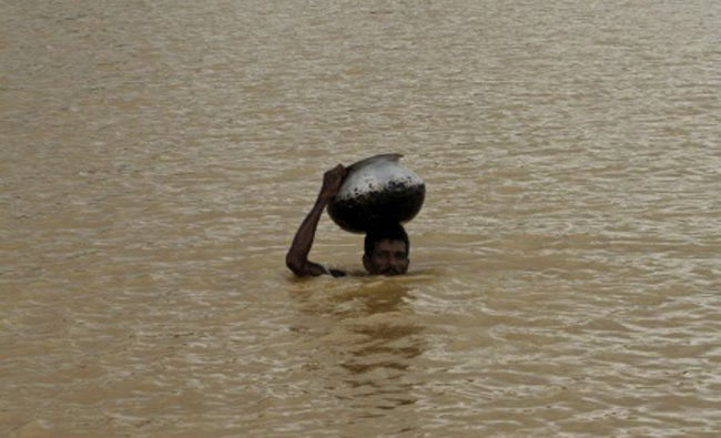 A villager on his way to collect drinking water wades through flood waters carrying a vessel...