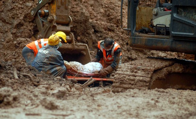 NDRF personnel with a body of a victim of landslide at Malin village on Thursday...