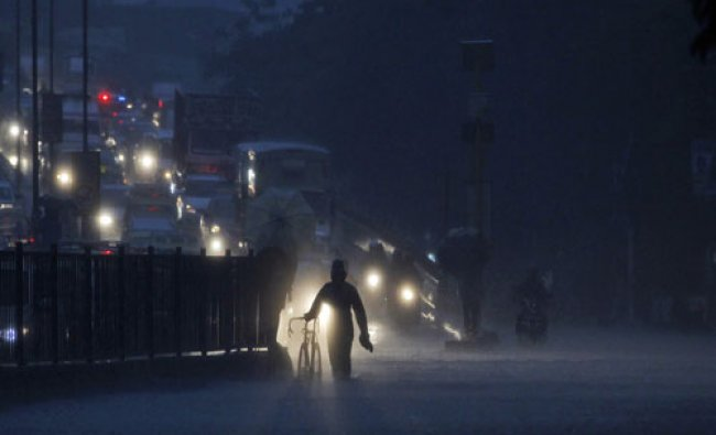 An man holds a cycle and wades through a flooded street as it rains in Mumbai. Heavy rainfall...