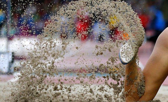 A jumper raises sand during the women\'s long jump final at Hampden Park Stadium during the...