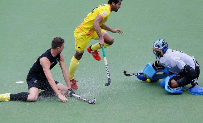 Alex Shaw of New Zealand is blocked by goalkeeper Sreejesh Parattu Raveendran of India ...
