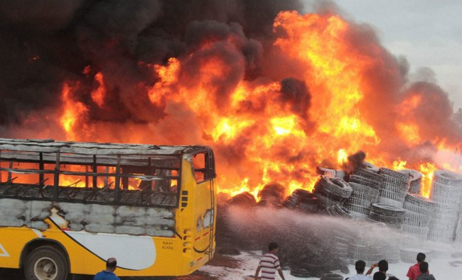 Fire fighters try to control a fire from tyre godown at Chamarajpet, in Bengaluru ...