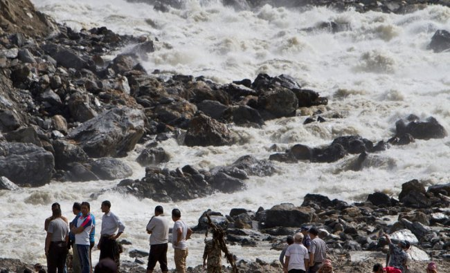 People stand at the banks of the River Sunkoshi near the site of a massive landslide in Nepal ...