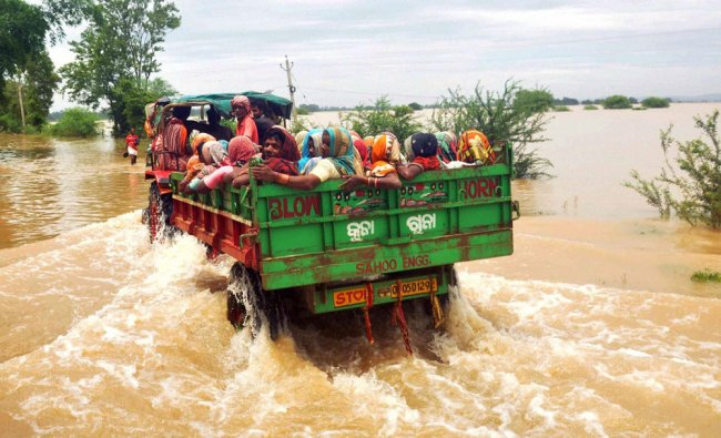 People shift by a tractor from a flooded village in Khurda district of Odisha ...