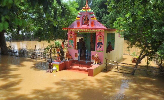 A temple gets submerged in flood waters of river Daya in Kapudia village near Jatni ...