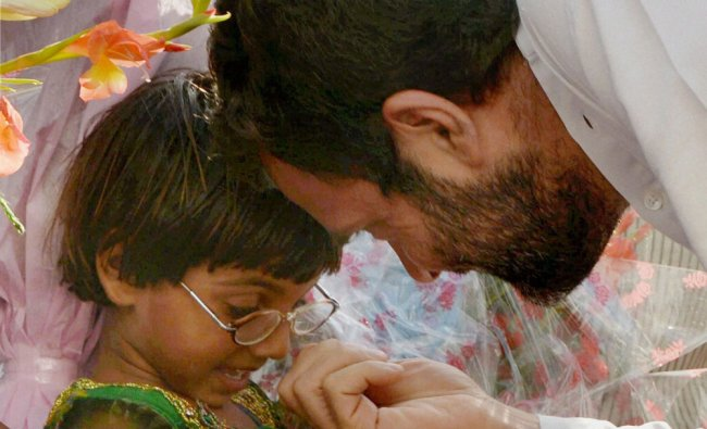 Rahul Gandhi interacts with a girl child during the inauguration of Indira Gandhi Eye Hospital ...