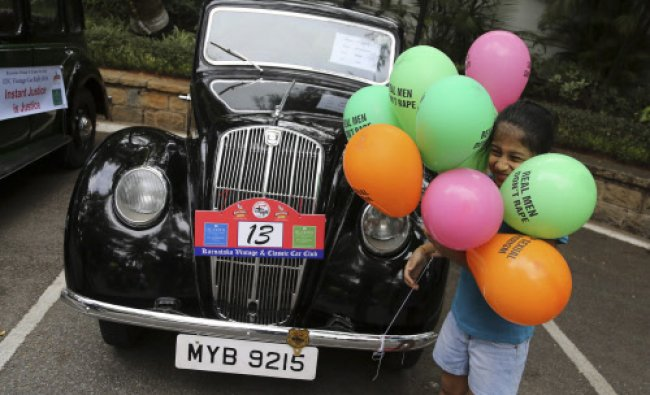 A girl plays with colored balloons printed with messages denouncing rape next to a 1948 Morris...