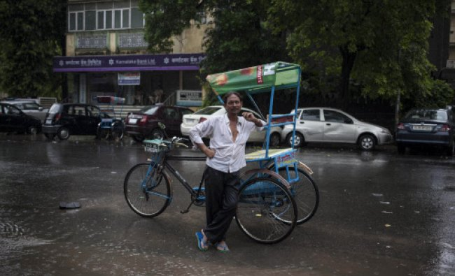 An rickshaw puller stands leaning against his cycle rickshaw in the rain as he awaits a customer...