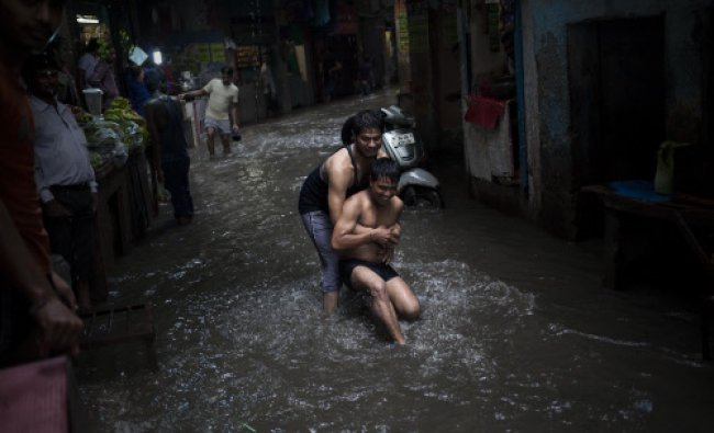Two young men play in a narrow street flooded during monsoon rains in New Delhi. India receives...