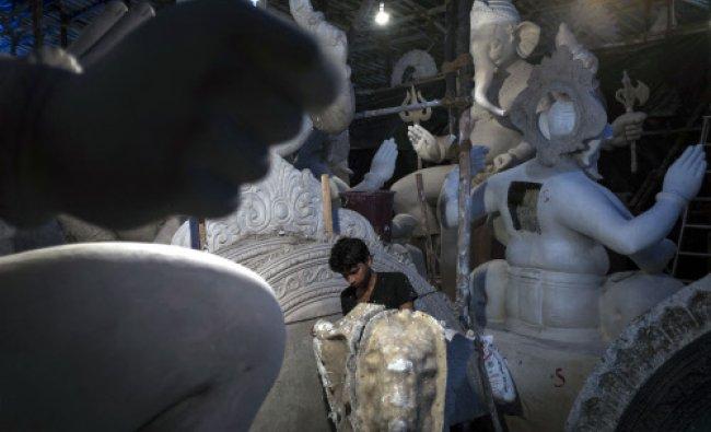 An artisan works on an idol of elephant god Ganesh, the deity of prosperity, at a workshop...