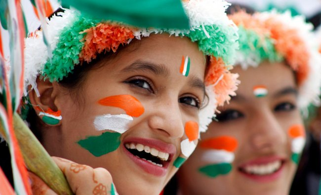 Schoolgirls dressed in the colors of the Indian national tricolor flag participate in rehearsals...