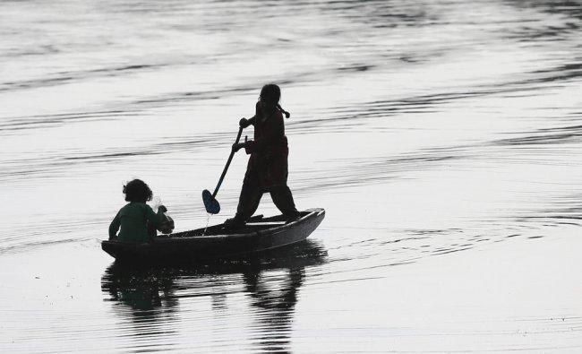 A Kashmiri girl rows a Shikara, or traditional boat, on the Dal Lake in Srinagar, India...