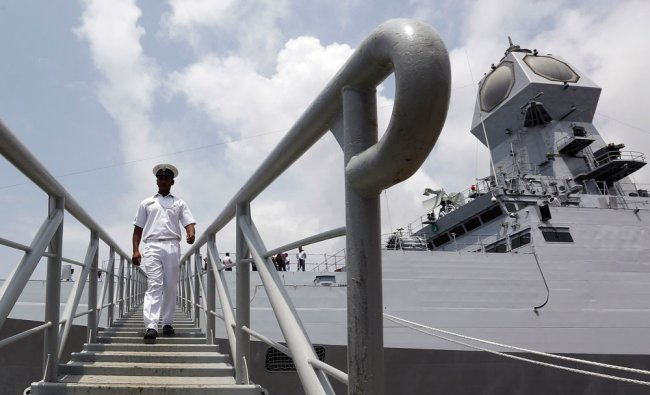 An Indian Navy officer walks the gangplank of the INS Kolkata during a media preview in Mumbai...