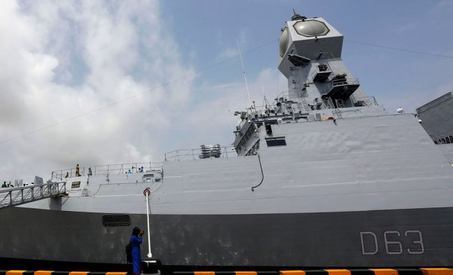 A woman takes pictures of the INS Kolkata during a media preview in Mumbai, India, Wednesday...