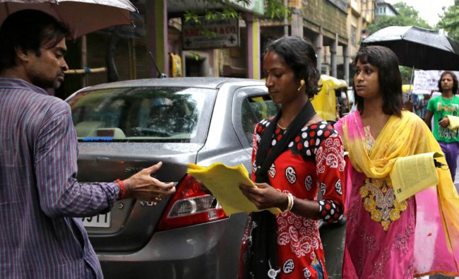 Indian sex workers distribute leaflets to commuters as they walk in a rally demanding social...