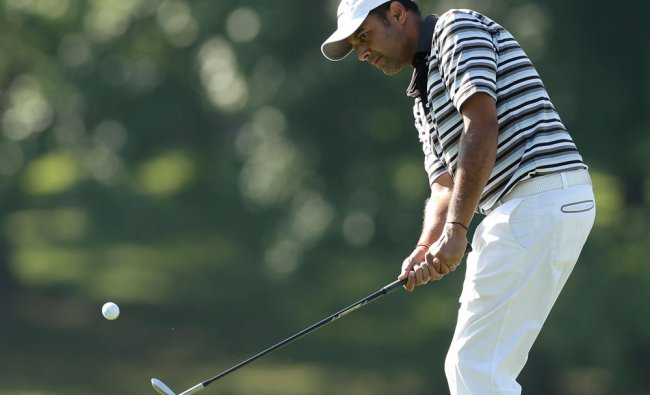Arjun Atwal, of India, chips to the ninth green during the first round of the Wyndham...