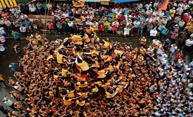 Indian youth form a human pyramid to break the \'Dahi handi,\' an earthen pot filled with curd...