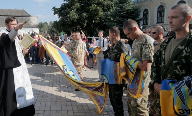 A priest blesses volunteers of battalion \'Donbas\' as they hold battalion flags during a blessing ...