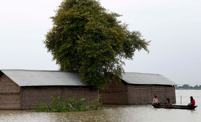 Villagers in a boat move to safer places through the flooded areas of Jhargaon in Assam...
