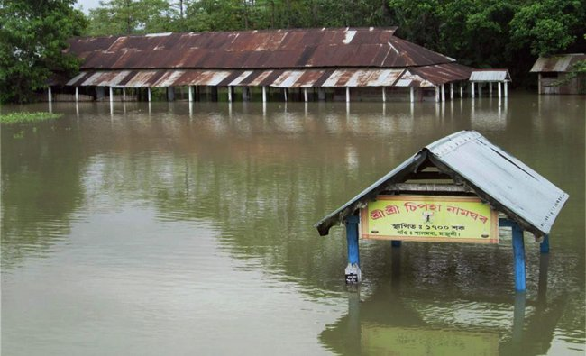 Houses inundated by flood waters at Majuli in Assam ...