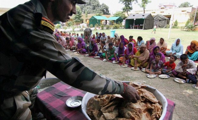 An Army jawan distributes food to people of border villages who are affected by Pakistani shelling .