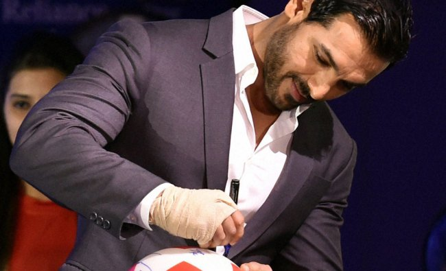 John Abraham, signs a football during the launch of the Indian Super League, in Mumbai ...