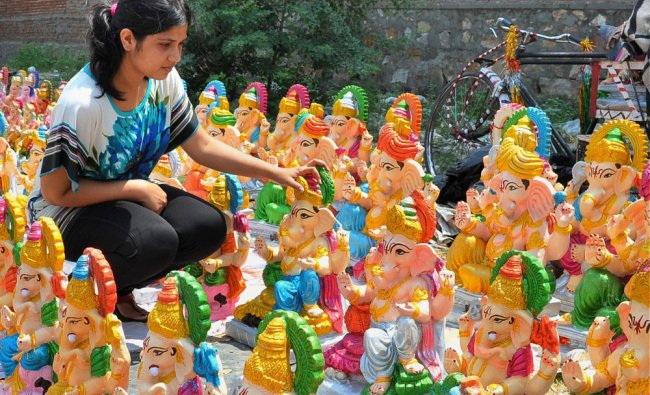 A young girl viewing Ganesh statues for sale on the eve of the Ganesh Chaturthi in Jaipur ...