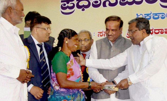Siddaramiah presenting kit to a beneficiary during launch of \'Pradhan Mantri Jan-Dhan Yojana\' ...