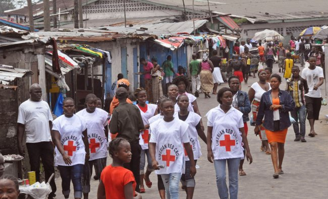 Red Cross workers walk through an Ebola hit area in Monrovia, Liberia ...