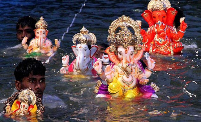 Devotees immerse idols of Ganesha into a lake in Thane , Mumbai on Saturday.