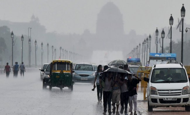 Childrens walks with an umbrella as it rains at Rajpath in New Delhi on Sunday....
