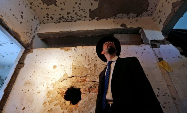 Rabbi Moshe Gourarie from New Jersey looks at a wall riddled with bullet marks from the 2008...