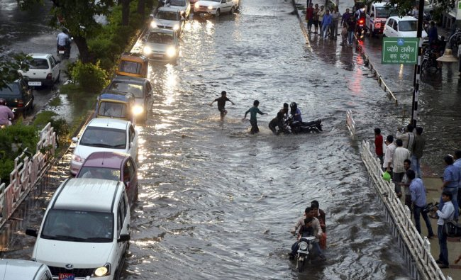 Vehicles ply on a waterlogged road after heavy rains in Bhopal on...