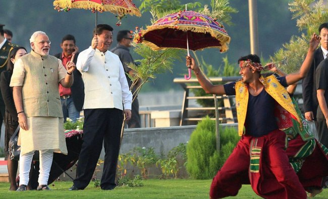 Narendra Modi and Chinese President Xi Jinping, holding umbrella watch a cultural performance...