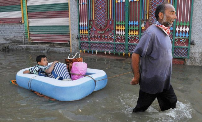 A man pulls an inflatable raft with his son, through the flood water...