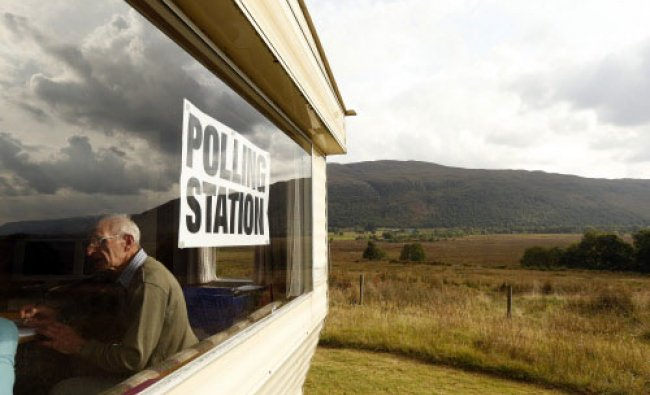 Poll clerk George MacKay sits in the Coulags caravan polling station, in the Scottish ...