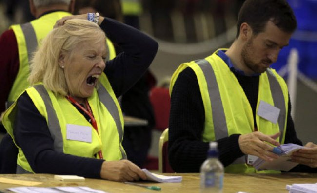 A counting staff member yawns as they count ballot papers through the night in the Scottish...