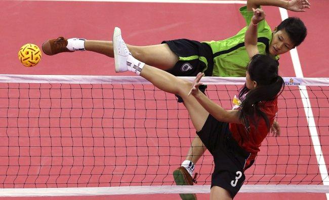 Myanmar\'s Phyu Phyu Than, top, kicks a ball as Laos\'s Koy Xayavong front, blocks during...
