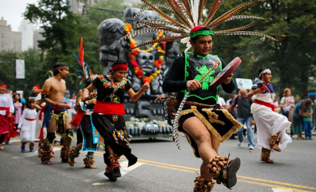 People dance during a rally against climate change in New York September 21, 2014. An...