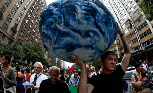 A man carries an inflatable earth balloon along West 72nd Street during the People\'s Climate...