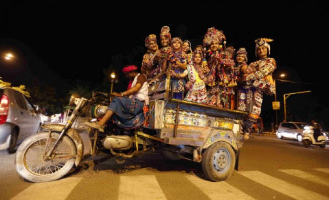 Dancers wearing traditional attires pose as they stand in a cart driven by a motorcycle...
