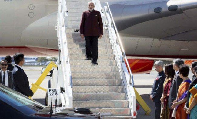 Prime Minster Narendra Modi walks down the airplane steps as he arrives at JFK airport ...