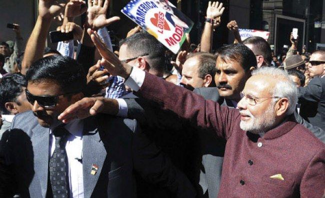 Prime Minster Narendra Modi (R) waves at people on the street in New York September 26,...
