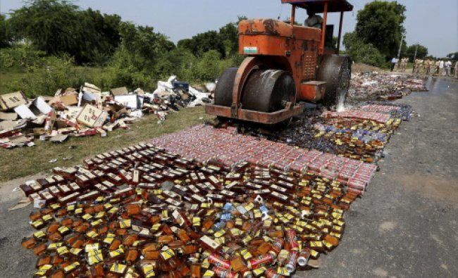 A road roller crushes a large number liquor bottles seized by the police from the...