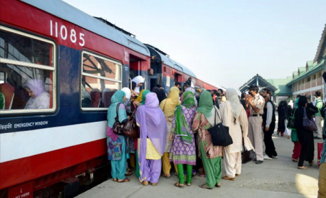 Female Passengers board a train after train services were partially resumed following...
